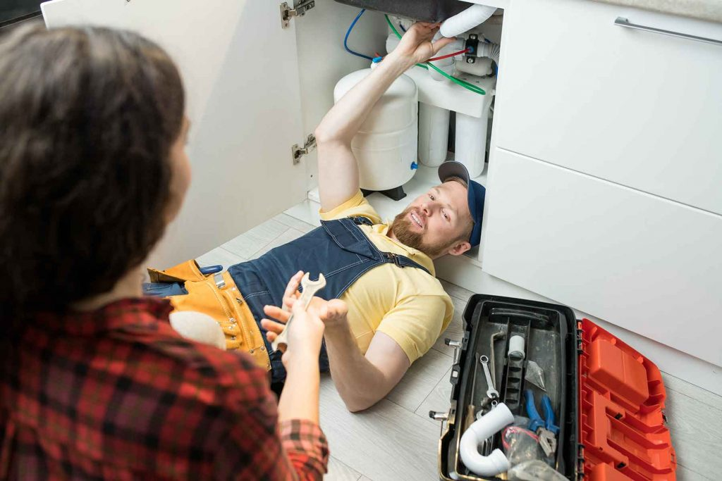 handsome-plumber-fixing-sink-pipe-2DM4WGS.jpg