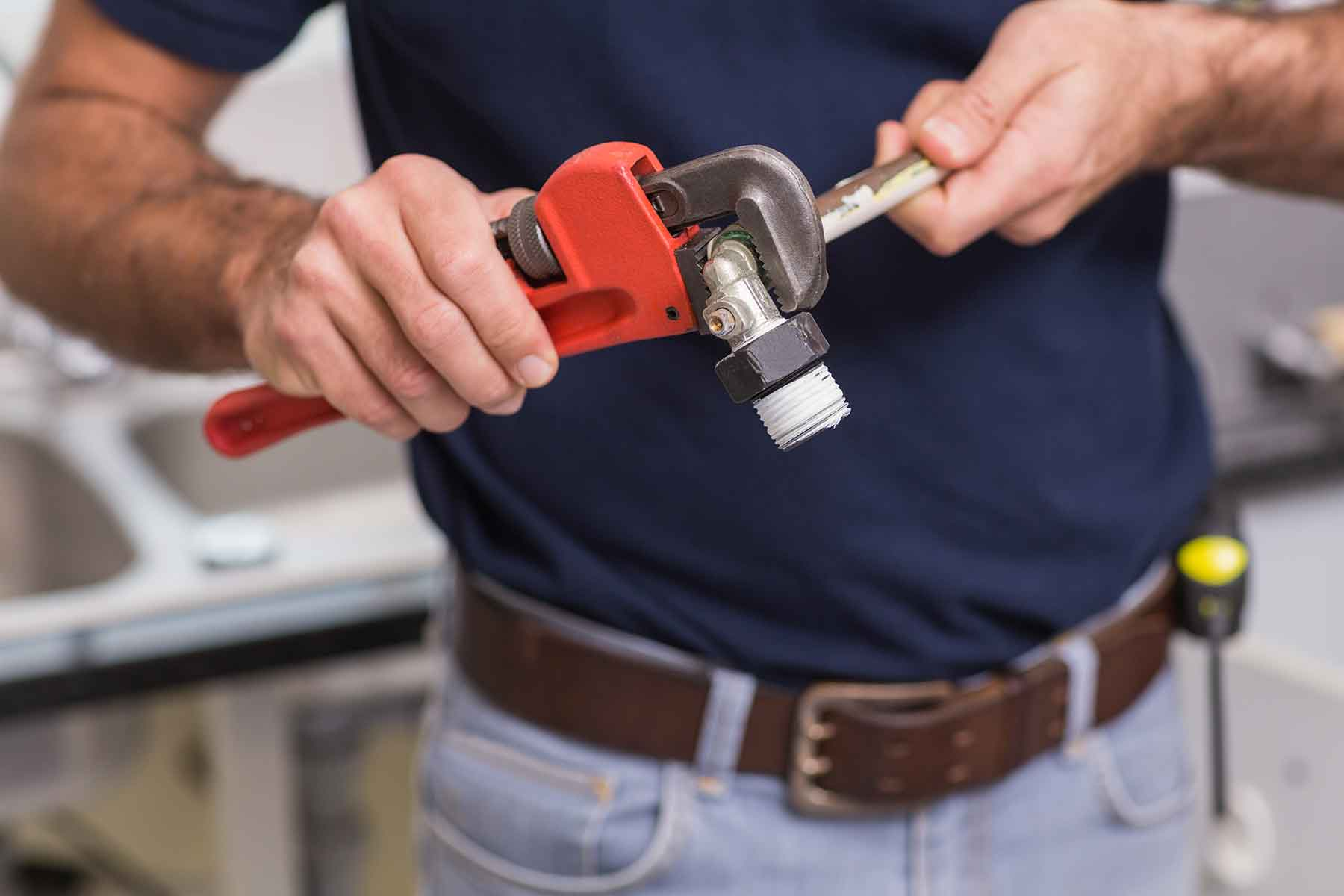 plumber-fixing-pipe-with-wrench-in-the-kitchen-PW55SHB.jpg